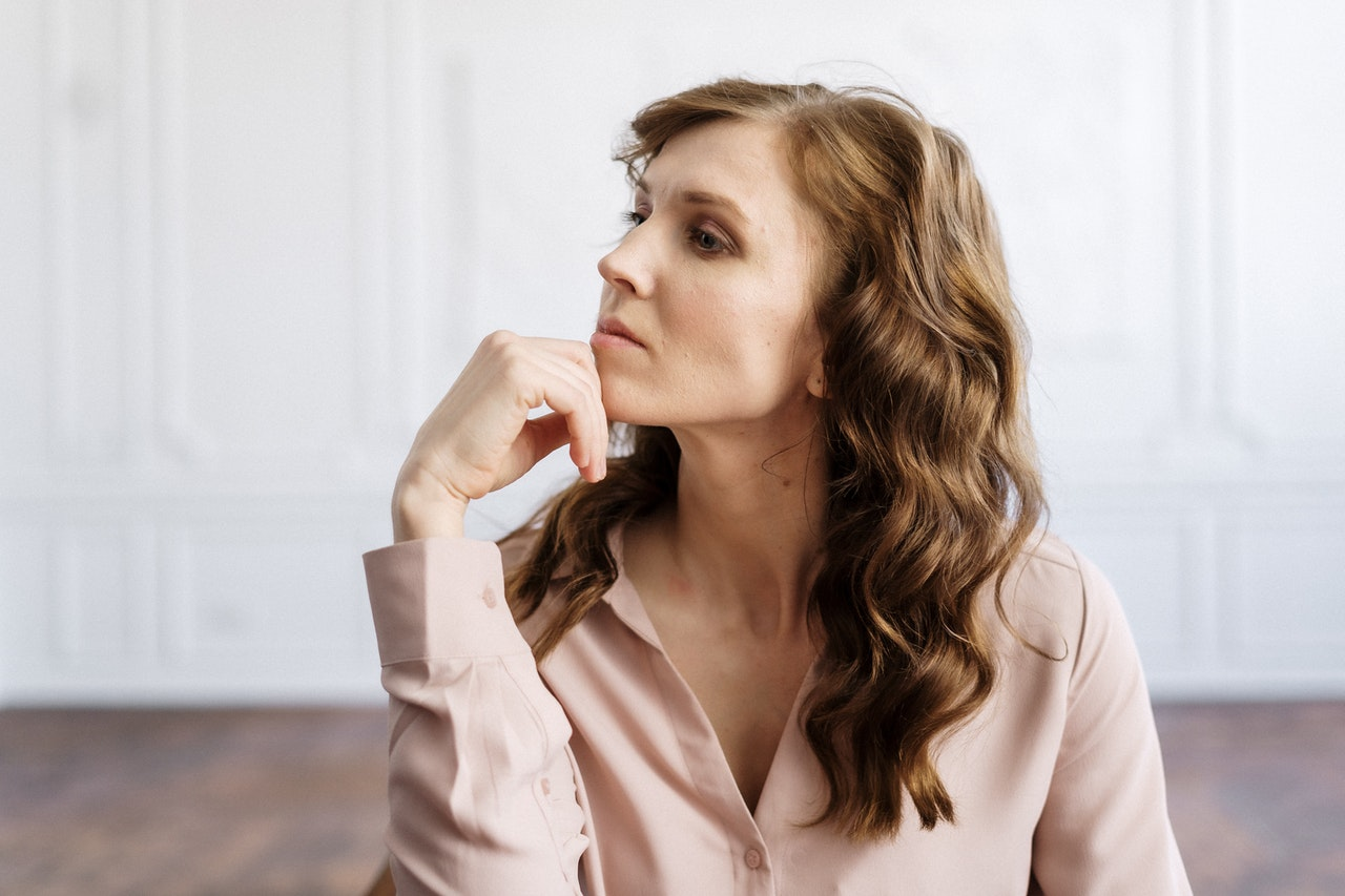 a women sat with chin on head thinking