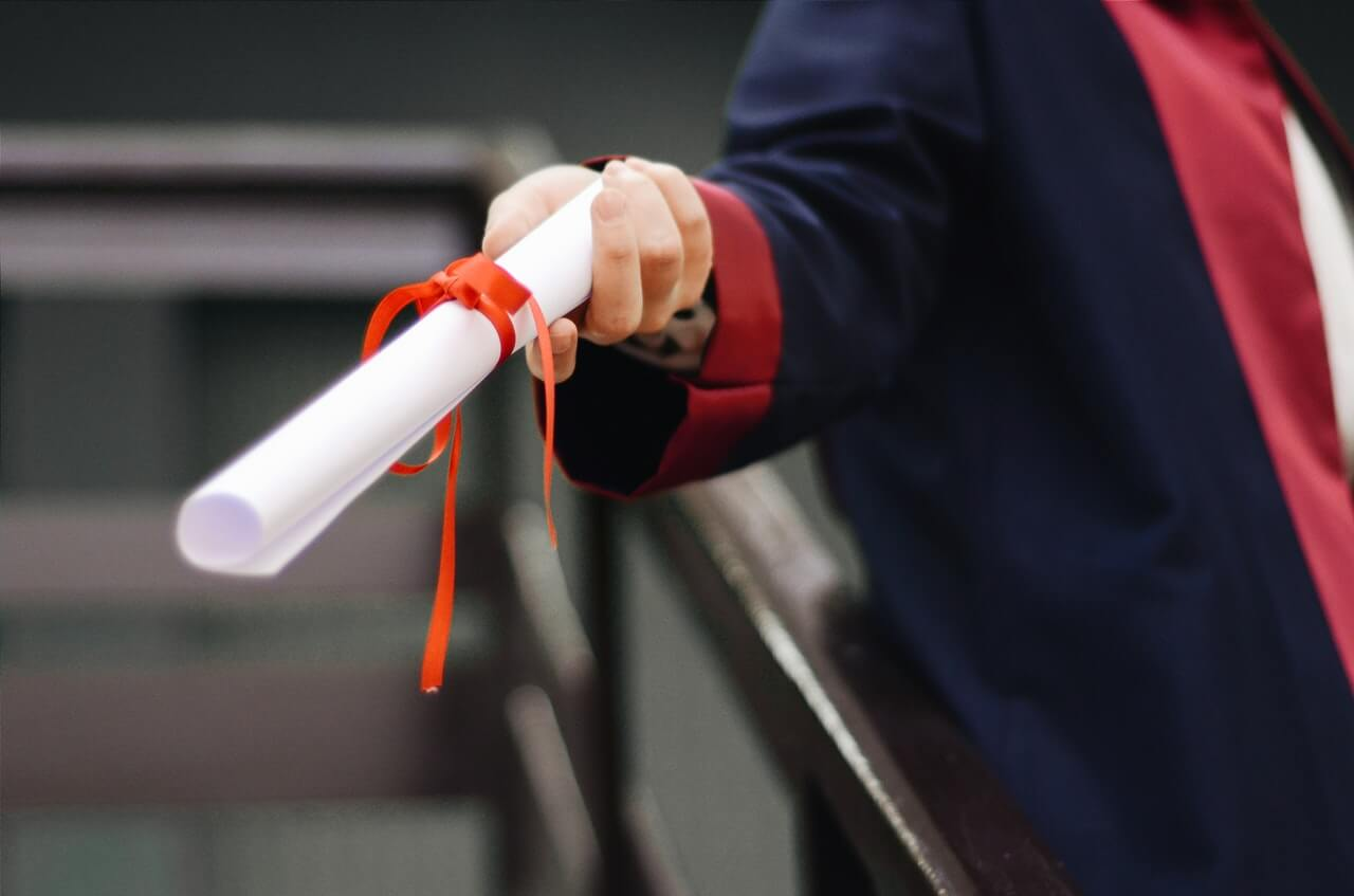a graduate holding a degree certificate dressed in an academic gown